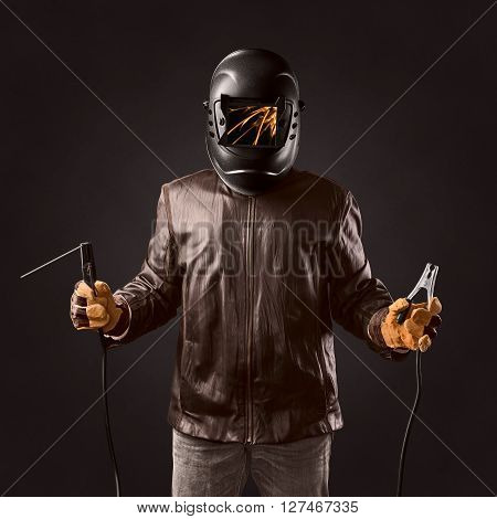welder in protective helmet with welding apparatus in the hands on brown background