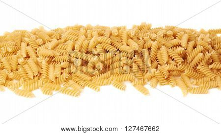 Line made of dry rotini yellow pasta over isolated white background