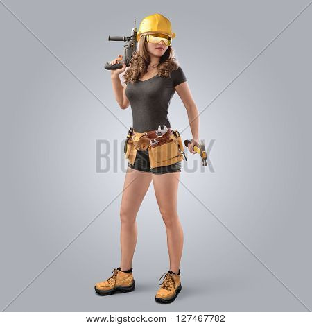 worker girl in a helmet with drill and hammer on grey background
