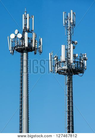 Two telecommunications towers with satellite dishes and antennae fro transmitting and receiving broadcasting signals against a sunny blue sky with copy space