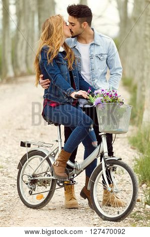 Beautiful Young Couple In Love On Bike In The Park.