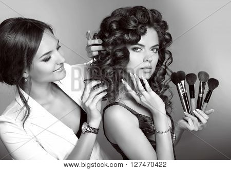 Curly Hair. Beauty Makeup. Professional Artist Woman Applying Hairstyle Sensual Brunette Girl Model