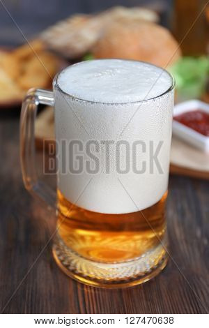 Glass mug of light beer with snacks on dark wooden table, close up
