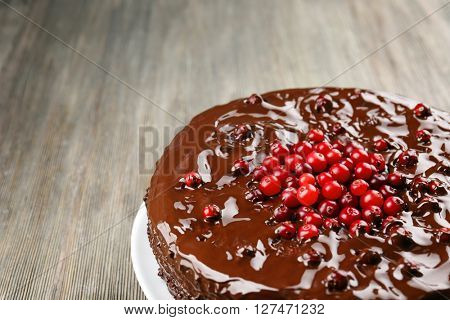 Chocolate cake with cranberries on wooden table, closeup