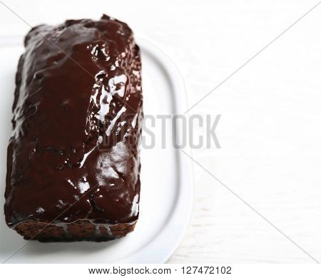 Chocolate cake with icing on white table