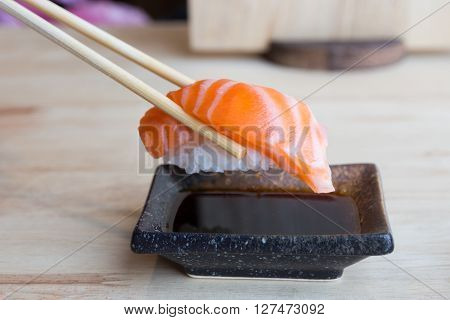 Raw salmon on rice with chopsticks dipped sauce - japanese food concept
