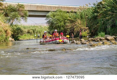 JORDAN RIVER ISRAEL - OCTOBER 2: Group of teenagers rafting on the Jordan River in Israel on October 2 2015