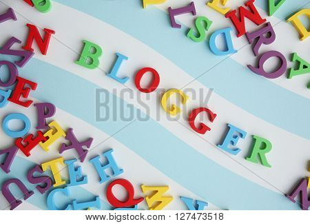 Word BLOGGER made with colorful letters on striped background