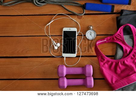 Sport equipment and clothes with mobile phone on  wooden background