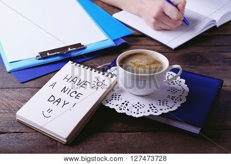 Female hands writing in notebook near cup of coffee and note HAVE A NICE DAY on wooden table closeup