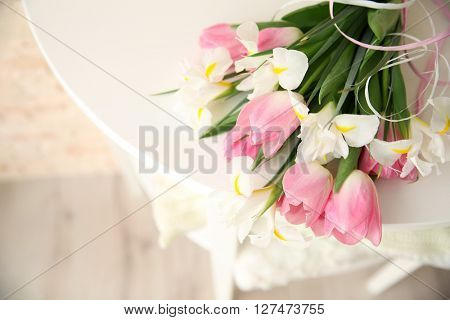 Beautiful bouquet of fresh tulips and irises on wooden table closeup