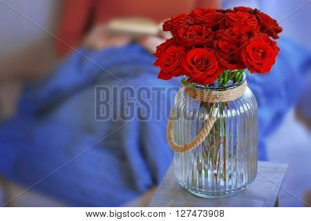Glass jar of red roses beside woman reading book on sofa