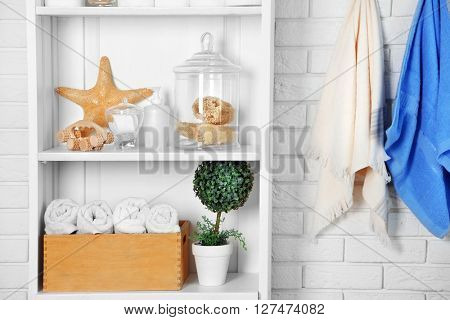 Bathroom set with towels, starfish and sponges on a shelf in light interior