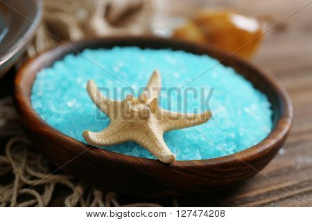 Spa concept. Bowl with blue sea salt and starfish, close up.