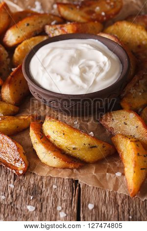 Baked Potato Wedges And Sauce Close-up On The Table. Vertical