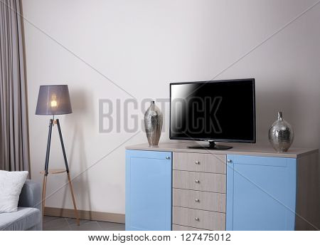 Modern living room with big cupboard and TV.
