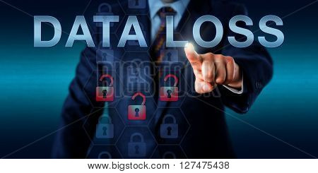 Network administrator is pressing DATA LOSS on a touch screen interface. Business metaphor and information technology concept for loss of data through crime disaster failure or intentional action.
