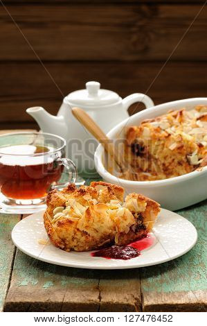 Panettone pudding and fresh black tea on shabby wooden background vertical
