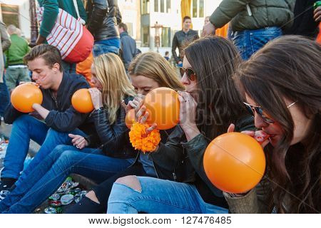 AMSTERDAM, NETHERLANDS on APRIL 26, 2015. City natives and tourists using lachgas during Queen's Day or King's day, Dutch annual national holiday, in the streets of Amsterdam, Holland