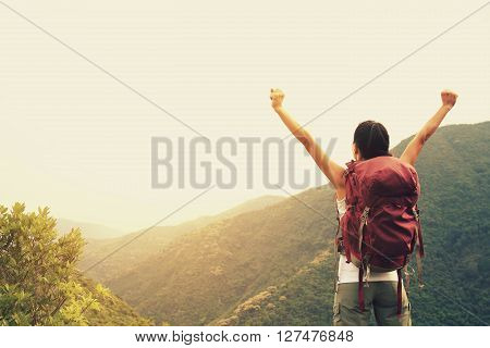 cheering young woman hiker enjoy the view on mountain peak cliff
