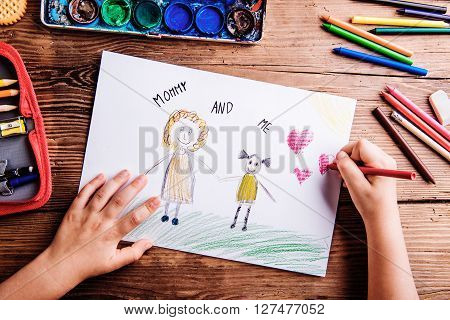 Mothers day composition. Hands of unrecognizable child drawing picture of her and her mother. Studio shot on wooden background.