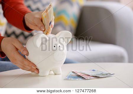 Female hand putting money into piggy bank closeup