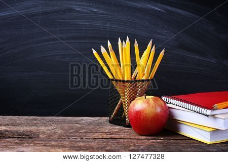 Set of pencils in metal holder, notebooks and apple on blackboard background