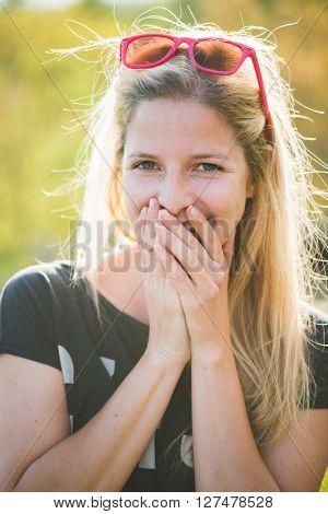 Blonde woman grimacing. Summer outdoor portrait.