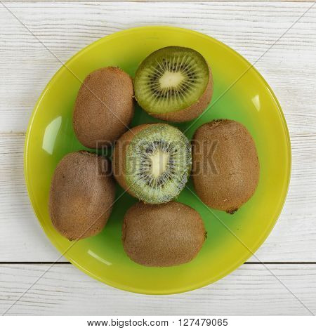 Halves and whole kiwi placed on a plate. Top view. Helping digestion with enzymes. Boosting immunity. Creating alkaline balance. Naturally organic food. Premier Antioxidant Protection.