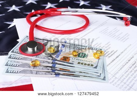 Stethoscope with medical form, dollar banknotes and pills on background of American flag
