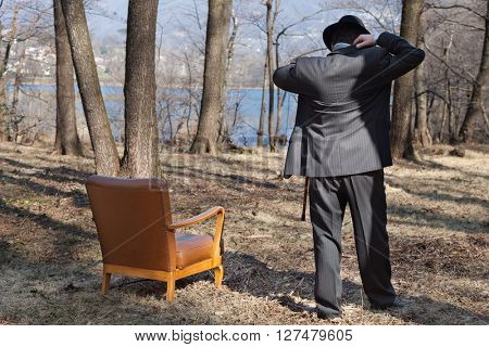 man elegant suit alone in the woods, rear view