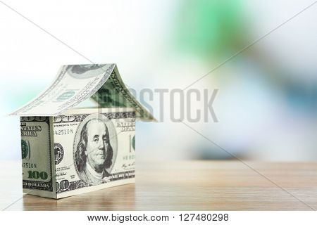 Money house on wooden table, close up