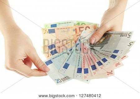 Fan of money in female hands isolated on white