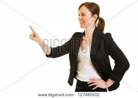 Smiling business woman holding up index finger for a virtual touchscreen