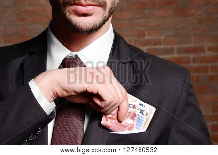 Attractive man getting euro banknotes out of suit pocket on brick wall background