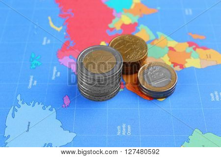 Euro coins on map background