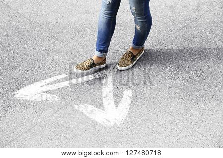 Female feet walking on road with white arrows