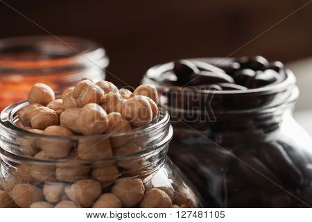 Chickpeas and red beans in glass jars macro shot selective focus