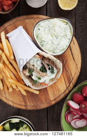 Greek gyros pita wrapped sandwich with meat stripes similar to turkish doner kebab