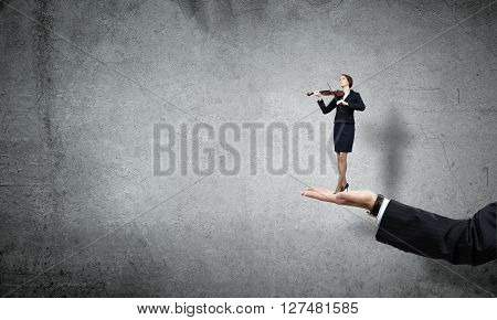 Big male palm holding small confident businesswoman that play violin