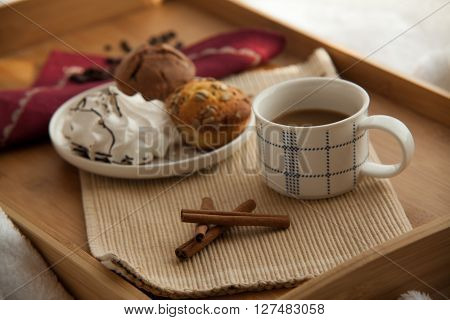 Sweet breakfast in bed served on tray with coffee and cupcakes