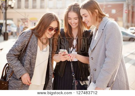beautiful young girl with her friends using a smartphone in the city