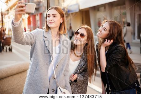 Lifestyle sunny image of best friend girls taking selfie on smartphone.