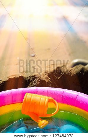 Summer vacation on the beach. Rainbow Children's inflatable pool with water and watering on the beach.