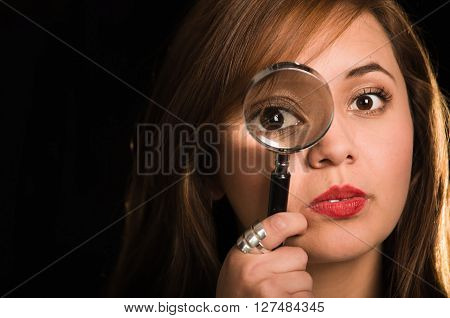 Young woman facing camera holding magnifying glass over right eye creating enhanced effect, black background.