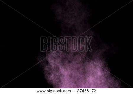 Abstract purple powder explosion on black background. Paint Holi.