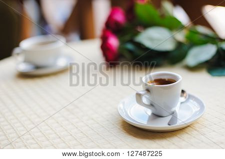 Cup of coffee on a table in a cafe. Bouquet of red roses and a second cup in the background. ** Note: Shallow depth of field