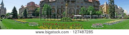 TIMISOARA ROMANIA - APRIL 22 2016: Panoramic view of historic buildings from Victory Square Timisoara including wolf statue with Romulus and Remus kids symbol of the city.