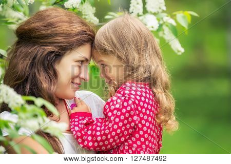 Outdoor portrait of mother and daughter in spring park