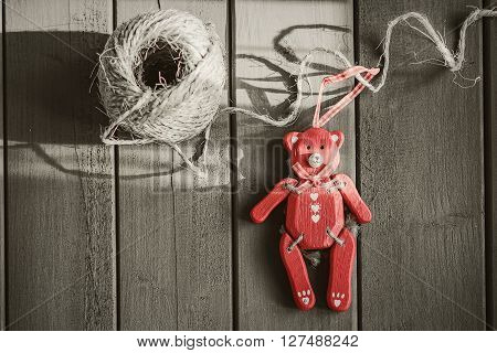 Red wooden bear on a dark wooden board.